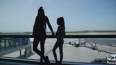 jitters : Silhouette of two sisters stand at the window of the waiting room of the airport with a view of the aircraft