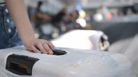 bavul : Close-up hand of a teenage girl with a youth manicure is lying on the suitcase on the airport conveyor belt background in blur. Girl waiting suitcase at the airport conveyor belt .