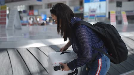 concourse : Girl teenager together with her mother take the suitcase from the airport conveyor belt.