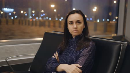 časová prodleva : A woman misses her night in the airport lounge waiting for your flight. Woman traveler with two suitcases sitting in the airport lounge.