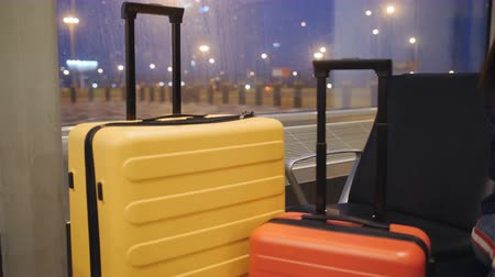 airport bus : Passengers baggage is in the airport lounge. Colorful suitcases passengers stand in the airport lounge at night.