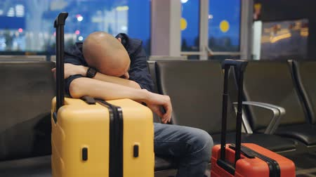 tiredness : A man sleeping leaning on the yellow suitcase in the airport lounge. The delay of the flight. Stock Footage
