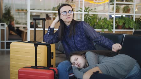 dois objetos : The mother and daughter in the waiting room of the airport sleeping on chairs