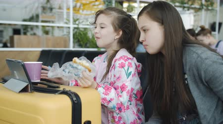 časová prodleva : Two girls watching the tablet and drink tea with biscuits at the airport.