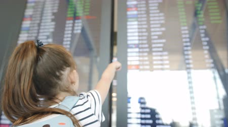 jóquei : The little girl looks up at the electronic schedule at the airport. Stock Footage