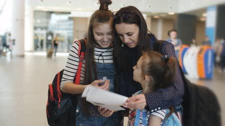 летчик : Mother with her daughters at the airport checks the tickets for the flight before signing up. Стоковые видеозаписи