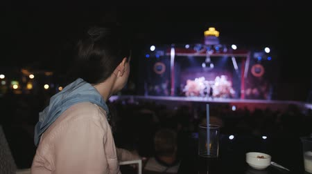 scena : Woman sitting at a table drinking a cocktail and watching the performance on stage.