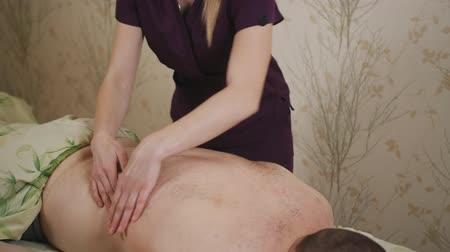 протирать : Female masseur massaging the back of the man laying on the massage table. Стоковые видеозаписи