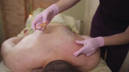 epilating : Beautician in Gloves Epilating Male Back with Sugaring. Male Beauty Treatment