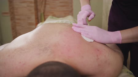chlupatý : Hair removal from male back. The procedure shugaring on a mans back.
