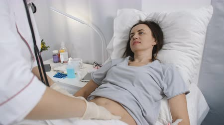 investigating : Woman doctor with gloves palpated the abdomen of the patient in the hospital. Stock Footage