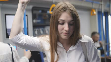 handrails : A woman in a subway car uses a smartphone. A woman riding in a subway car, clinging to the handrail and while away the travel time using smartphone.