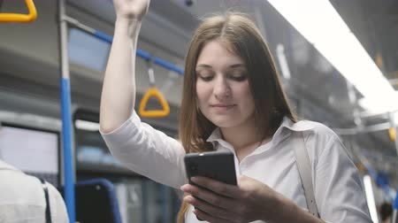 handrails : Young girl riding in a subway car and use the Internet in her smartphone. Stock Footage