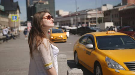 pronikavý : The girl with sunglasses standing at the road waiting for the arrival of a taxi.