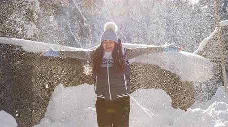 büszke : Happy woman enjoys Sunny winter morning, toss in the air spinning in snow and sparkling in the sun snowflakes.