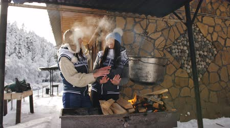 kamp ateşi : Two Women girlfriends on a clear winter day is prepared in the courtyard of a wooden forest house on an open fire. Stok Video