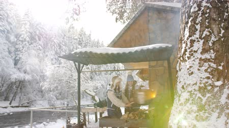 faház : Two women preparing food on the grill in the pot in a bright winter day near the forest wooden Chalet.