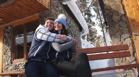 faház : Happy loving couple sitting on a bench near the winter Chalet in the mountains.