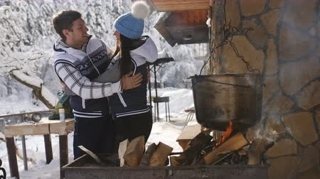 faház : Happy family in winter Chalet outdoor cook soup in a huge VAT over an open fire. Stock mozgókép