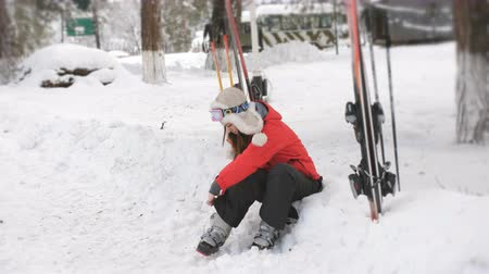 fasteners : Young woman ready for skiing. She puts on shoes sitting in the snow at a ski resort. Stock Footage