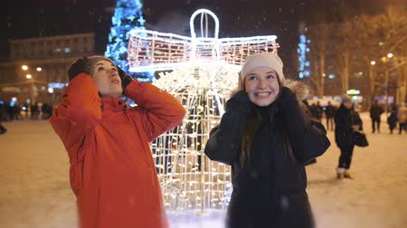 торжества : The Christmas festivities in the evening in the town square. Two friends taking a walk together.
