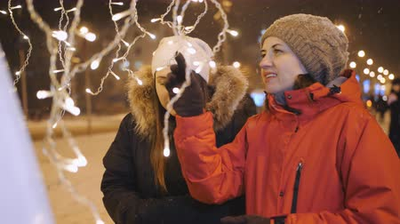 interessado : Two girls on a winter evening to view the Christmas decorations of the city.