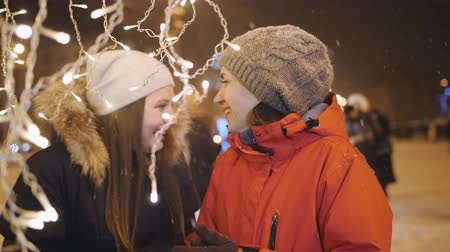 interested : Two women walk in evening winter city and view decorations, on Christmas eve. Stock Footage