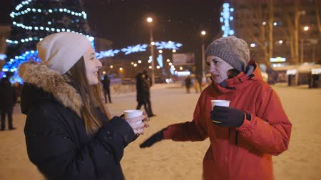 atender : Two girls in the center of the Christmas decorated city, drinking coffee and having fun. Stock Footage