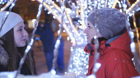 metáfora : Two girls on a winter evening stroll in the city centre, decorated for Christmas with bright lights and garlands.
