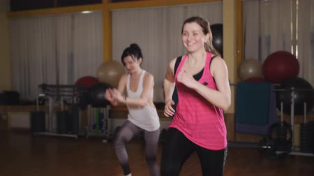 basic steps : Two beautiful sports girls squats in the gym. Two girls doing step aerobics front lunge with dumbbells on platform Stock Footage