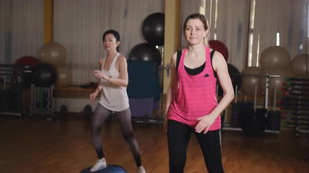 basic steps : Two female athletes in a sport dress perform a step-up raising of their legs. Stretching and paletes are performed by a professional instructor in a personal lesson. Stock Footage