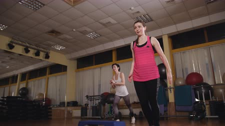 Two girls in the sports hall aerobic doing step aerobics.
