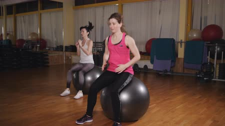 Athletic womans trains in the fitness room with Fitness ball.