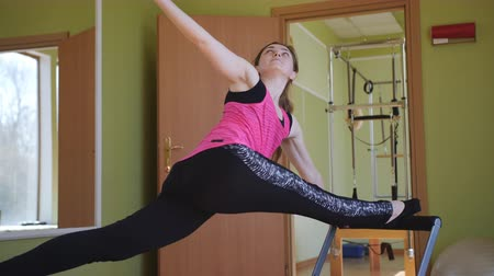 Pilates. Woman practicing stretching exercise on reformer in gym.
