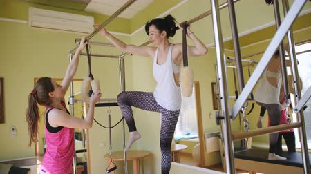 Casual women taking private pilates class with a trainer.