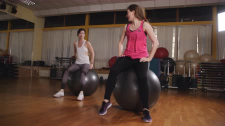 Athletic womans trains in the fitness room with gymnastic ball.