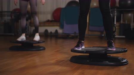 Two women doing exercise in the aerobic room with the use of core board. Stok Video