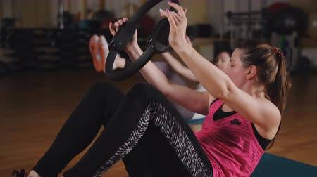 Two women in the gym doing Pilates exercises with the fitness rings.