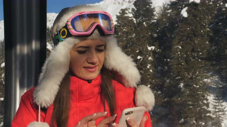 Woman making selfie on smartphone in the cabin ski lift. Stok Video