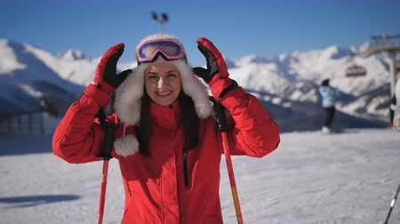Close-up portrait of female skier on mountain ski resort. Happy Woman in ski suit and ski goggles looking at camera and smiling.