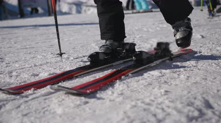 kötés : Girl zips up ski boots and sticks his feet in the ski mount before descending to the ski slopes.