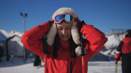 A woman skier at a ski resort comes up to the camera and removes the ski goggles. Stok Video