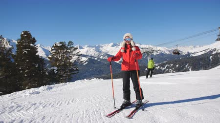 Female skier resting before the next descent from the mountain and admiring the winter scenery.