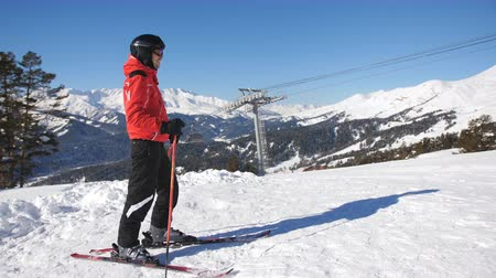 Male and female skiers on the mountain. A woman arrives on skis to male and the couple communicates.
