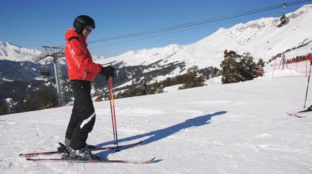 Male skier on a mountain top waiting for his beloved, which pulls up to him on the skis.