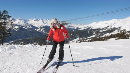 A woman afraid of a steep slope in the ski resort of side rises back leaning on the edge of the ski.