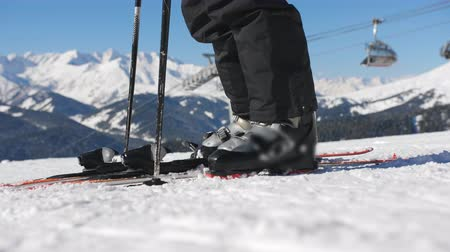 Fixing the ski boot. Skiing close up. Girl zips up ski boots and sticks his feet in the ski mount before descending to the ski slopes.
