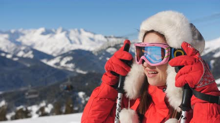 Close-up of Tired but happy Woman skier in the ski resort admiring the beautiful winter landscape. Stok Video