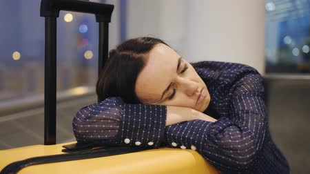 Businesswoman sleep on the wait area at the airport. Close-up of young attractive business female lying down on suitcase and sleeping.