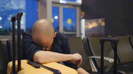 A man sleeping leaning on the yellow suitcase in the airport lounge. The delay of the flight. Stok Video